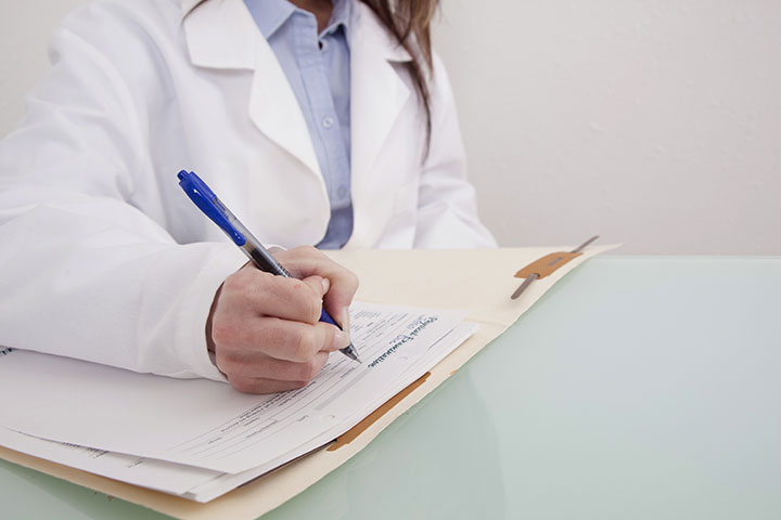 Doctor writing on patient chart.