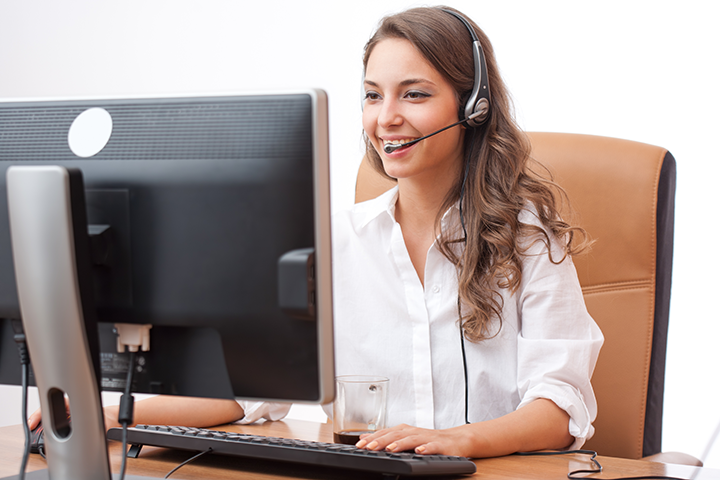 Smiling Woman at Keyboard with Headset